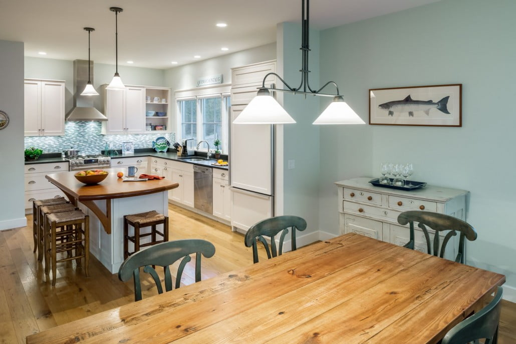 Custom brackets under the cherry island countertop reflect Craftsman-style detailing .  A glass tile backsplash, flat-panel painted cabinetry and wide plank oak flooring continue the beach cottage aesthetic.