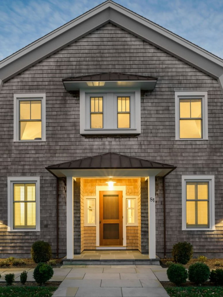 The front entry features a copper roof and double windows above, providing natural light to the rooms upstairs.