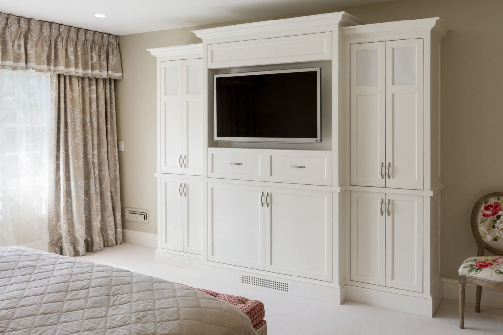 A custom storage unit houses the television in the master bedroom.  Note the grill at the bottom of the cabinet allowing for ventilation.