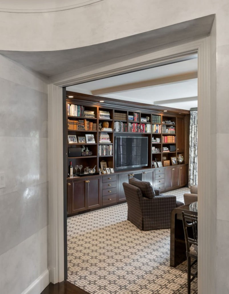 """A 20' custom built stained cherry cabinet with adjustable shelves houses a 60"""" television, home theater equipment, and a various selection of favorite books and family photos in the family room."""