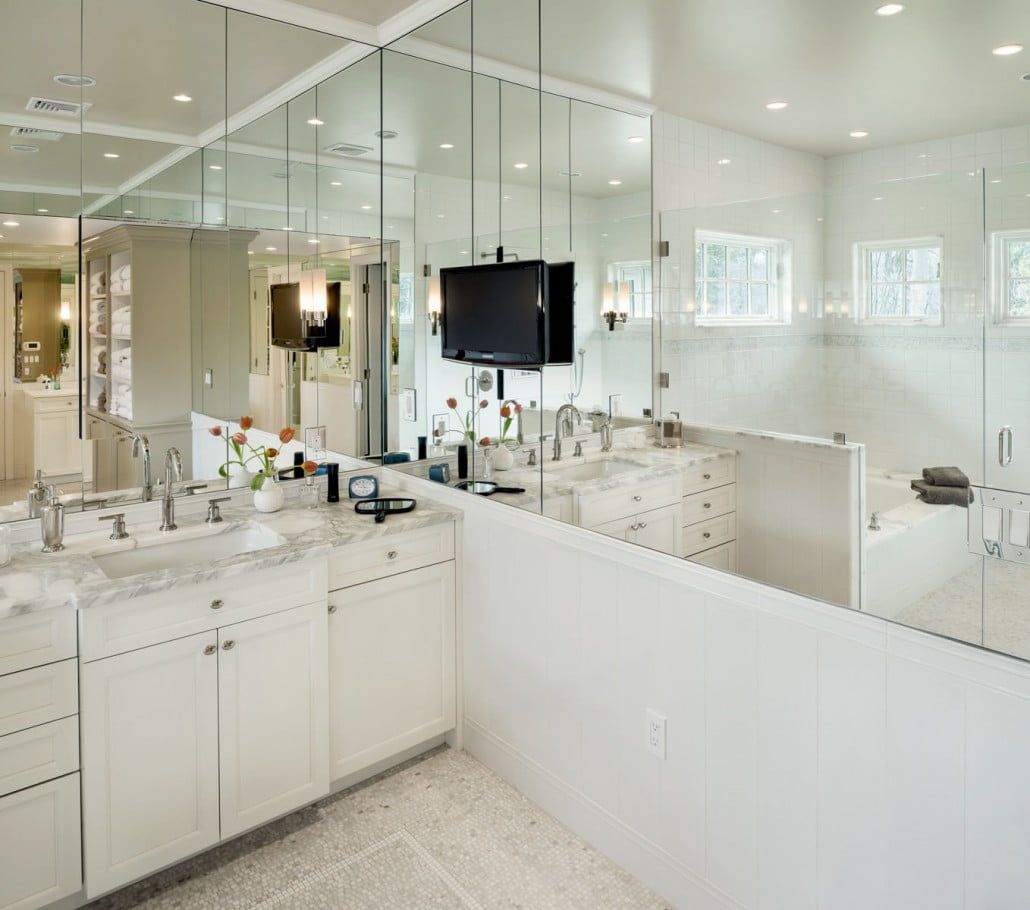 Mirrors, mirrors everywhere!  A recessed glass front medicine cabinet is barely visible above the sink.  A wall mounted television completes the room!
