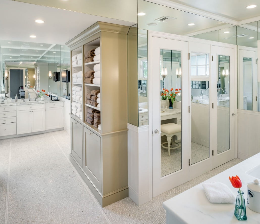 An addition on the home allowed for a large master bathroom.  A darker painted open linen cabinet takes center stage in the mirrored, light filled bathroom.
