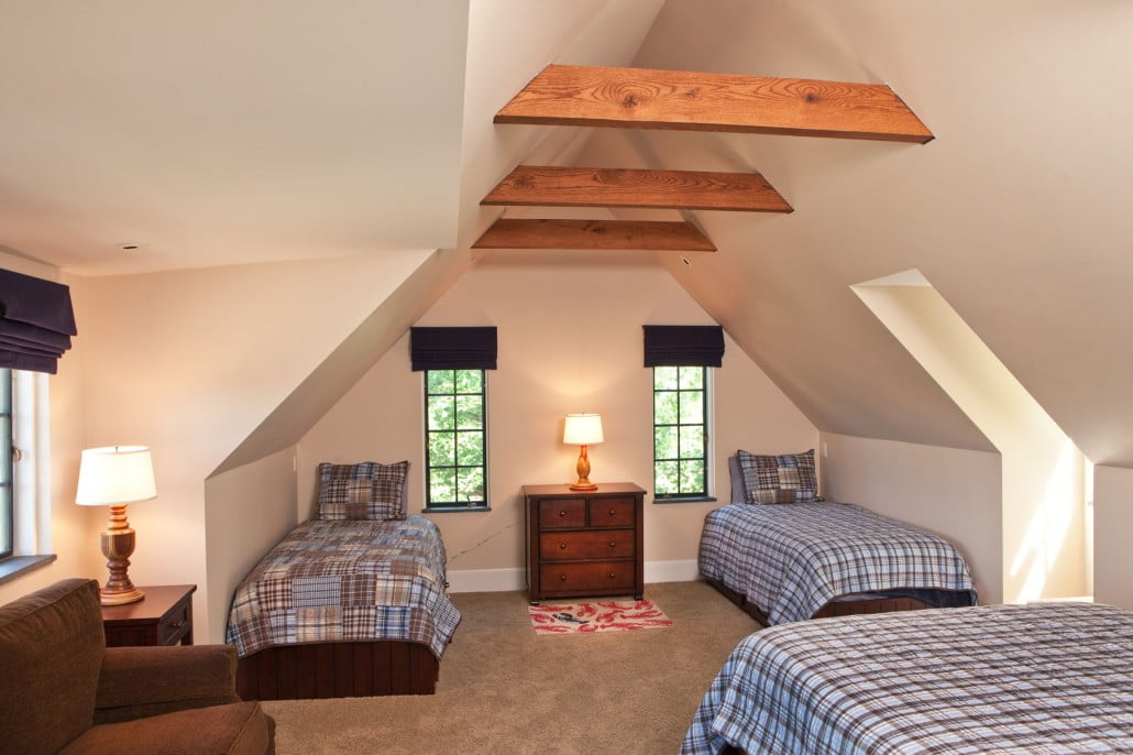 This large bedroom was created from two smaller bedrooms and a stairway above the family room.  The rafters are supporting oak rafters.