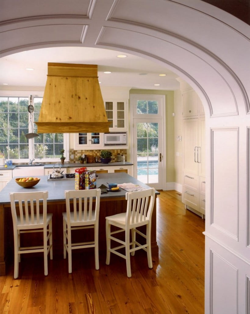 Another archway leads to the kitchen with a custom wood paneled exhaust hood over the island cooktop.